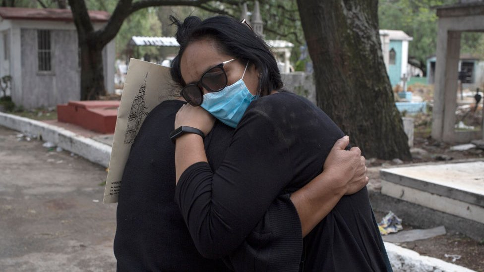 Dos personas abrazándose en un cementerio de México