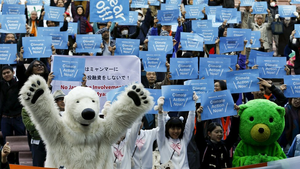 People hold placards demanding climate protection during a protest in Tokyo on Saturday