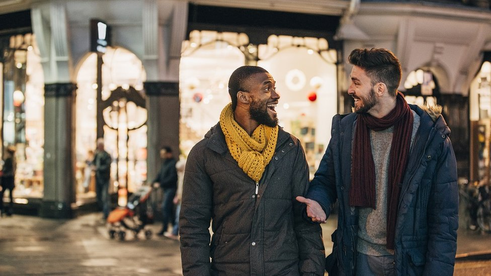 Dos hombres jóvenes hablan animadamente en una calle por la noche.