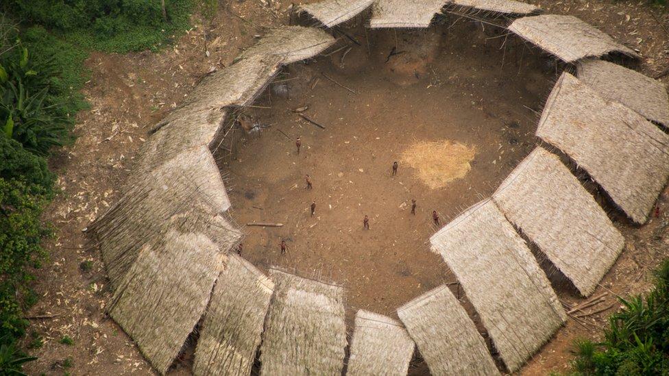 Maloca da comunidade Moxihatëtëma, formada por diveros telhados de palha voltados uns para os outros, com o centro aberto, em maio a clareira na floresta