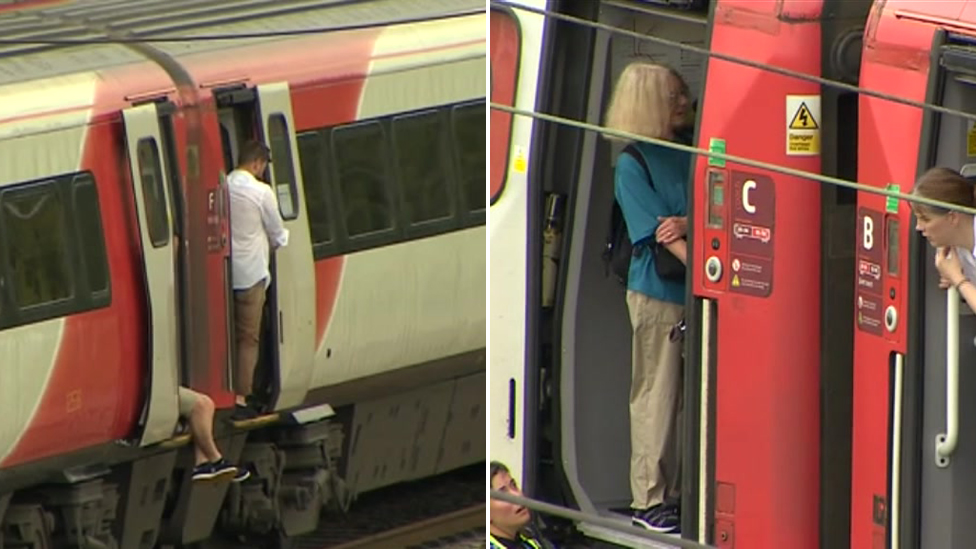 Passengers by open doors on stopped train