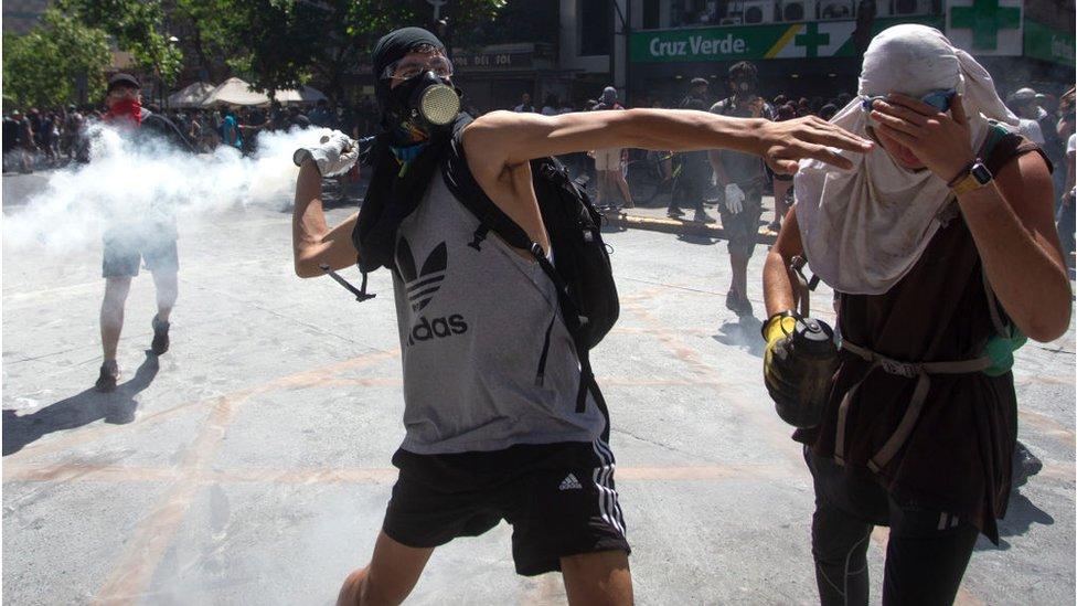 Manifestante lanza de vuelta el gas lacrimógeno tirado por la policía cerca del centro comercial Costanera Center