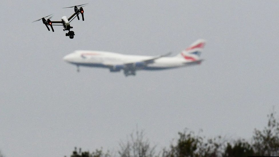 Drone flying in a West London park with a passenger plane in the background