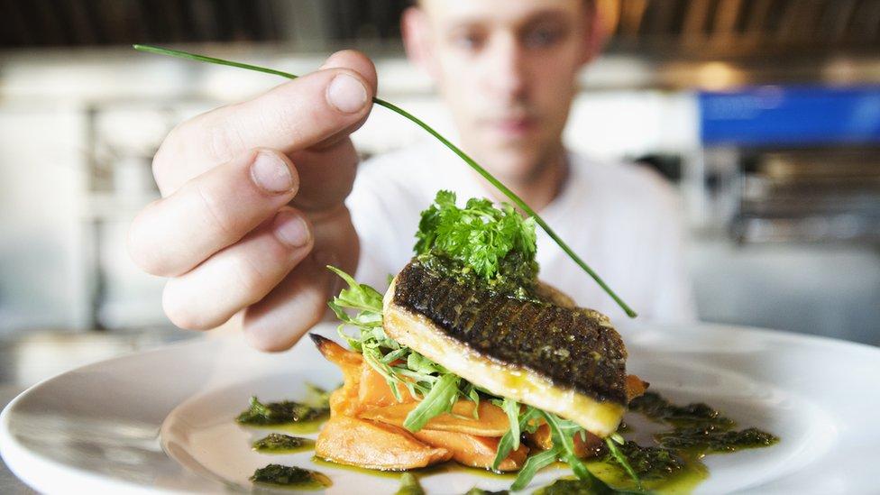 Un hombre decorando un plato.