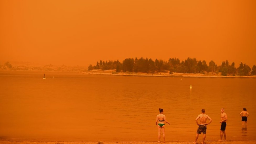 Swimmers stand near the water under a red sky at Jindabyne in New South Wales on 4 January