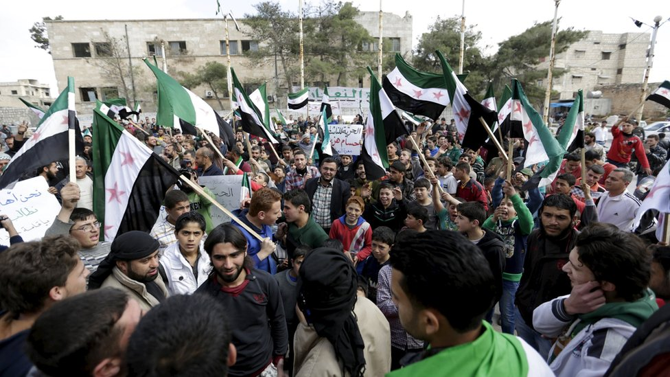 Protesters carry Free Syria Army flags and shout slogans during an anti-government protest after Friday prayers in the town of Marat Numan in Idlib province, Syria, March 11, 2016