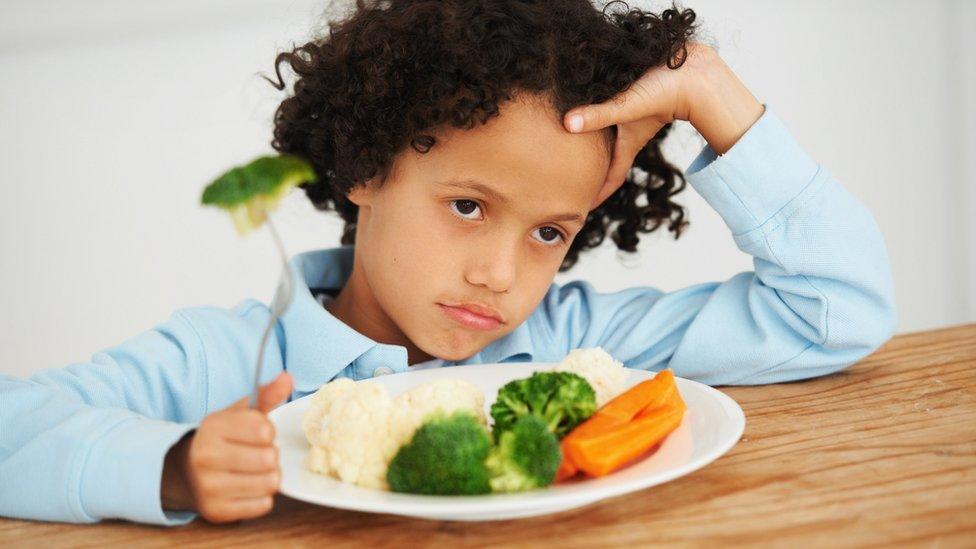 Niño negándose a comer vegetales.
