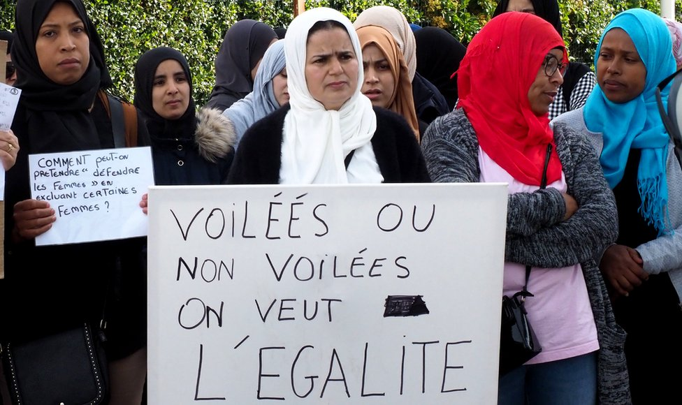 "Demonstrators outside a school in south-western France hold a placard reading: ""Veiled or not veiled, we want equality"" (28 May 2019)"