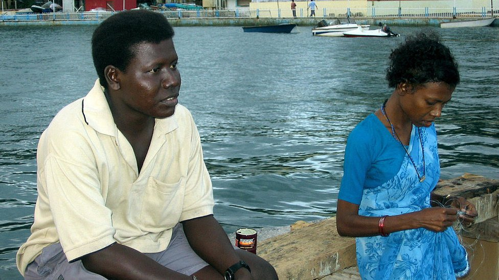 Mion (L), a member of near extinct Great Andamanese aboriginal tribe, sits with his sister, Ichika, by the waterfront in Port Blair.