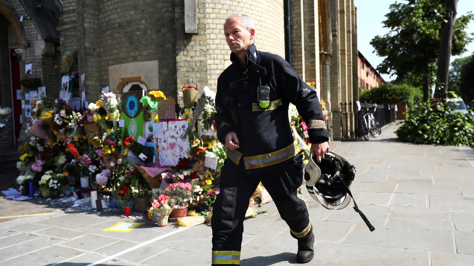 A member of the London Fire Brigade walks past tributes left for the victims