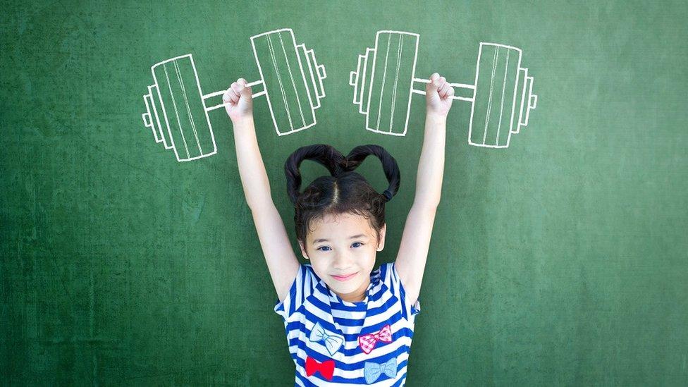 صورة تخيلية: بنت صغيرة سعيدة ومبتسمة تتخيل أنها قوية، ترفع أثقالا حديدية مرسومة بطباشير على سبورة حجرة مدرسية في الخلفية