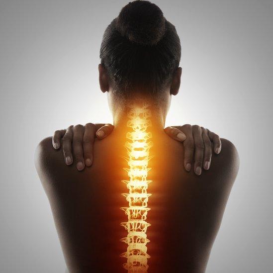 Una mujer de espaldas con la columna vertebral realzada