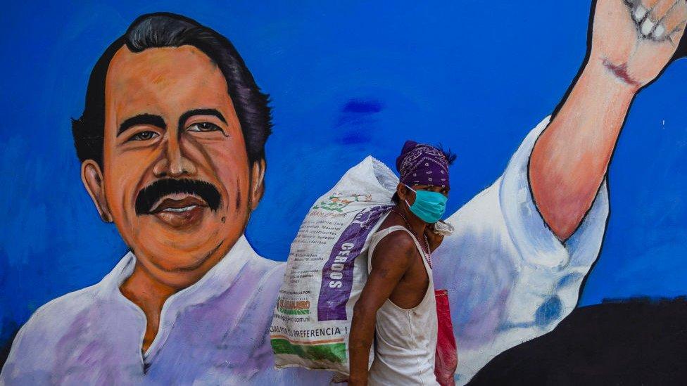 Hombre con máscara pasa frente a un mural con el rostro de Daniel Ortega.