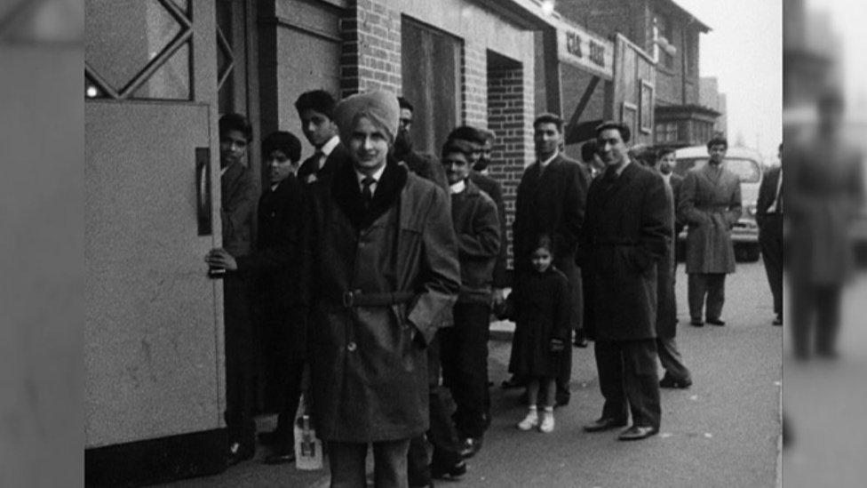 Indian men queuing outside a building