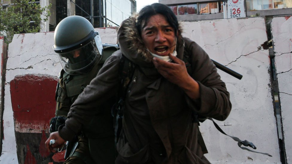 Manifestante durante las protestas de este sábado junto a un carabinero.