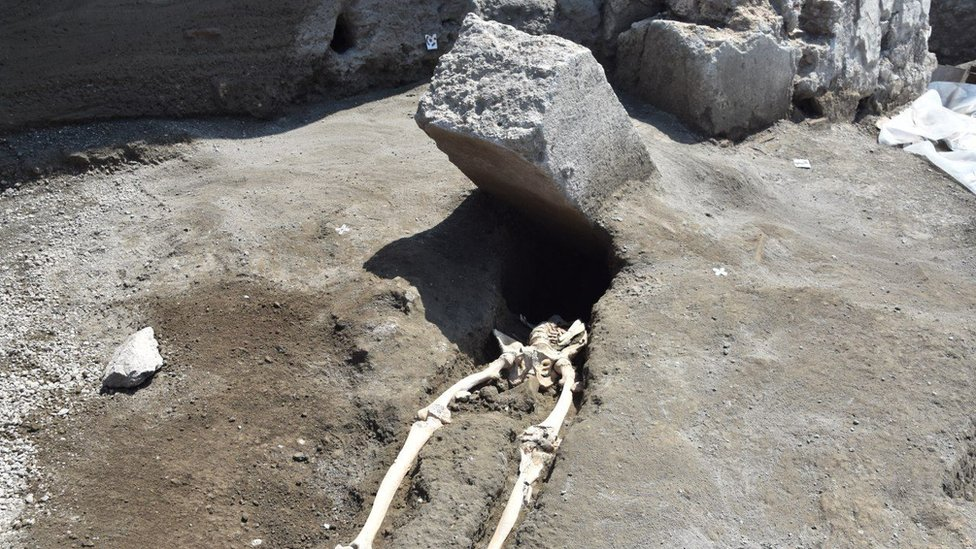 The skeleton of a victim of the eruption that destroyed Pompeii, shown with a huge boulder where his head should be