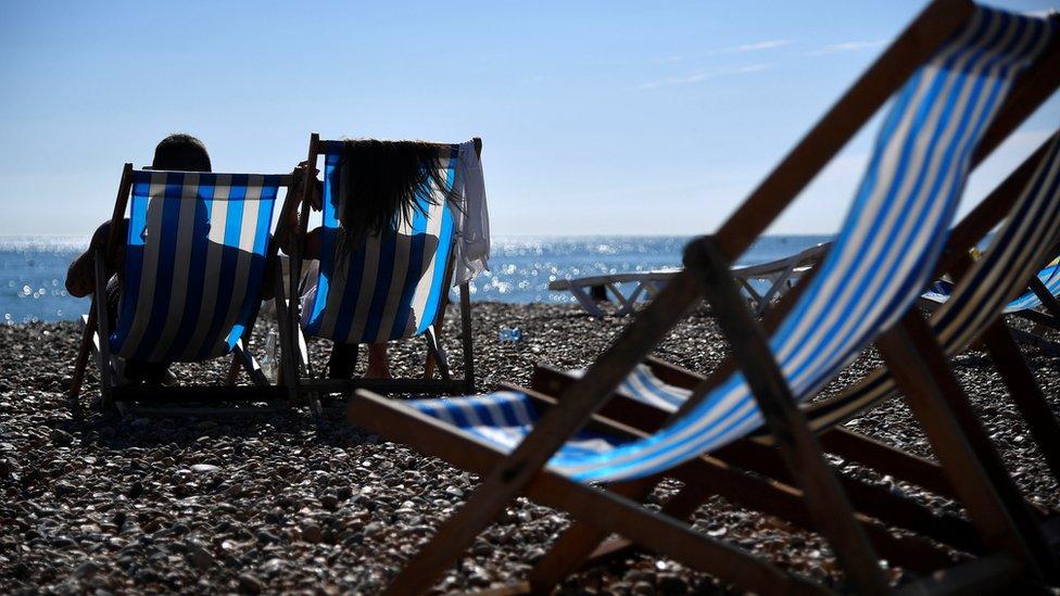 Beachgoers enjoy the hot weather
