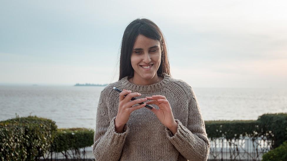 Milagros Costabel con su celular, por detrás se ve el Río Uruguay
