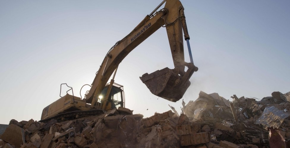 A bulldozer clears debris from buildings demolished by authorities in a migrant housing area on the outskirts of Beijing.