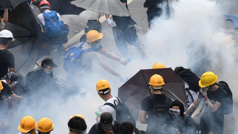 Manifestantes reaccionan al lanzamiento de gas lacrimógeno por parte de la policía en Hong Kong, junio 12, 2019