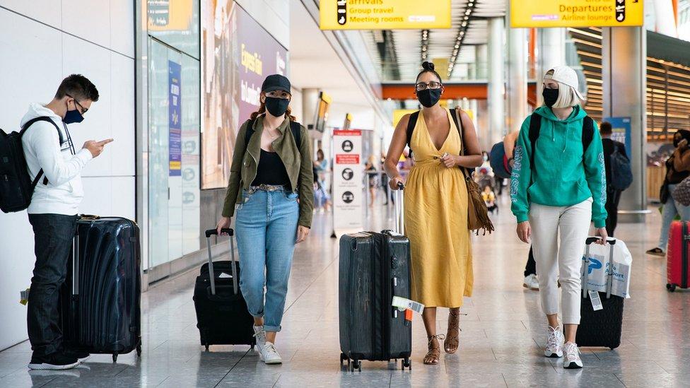 Three women in masks arriving at Heathrow