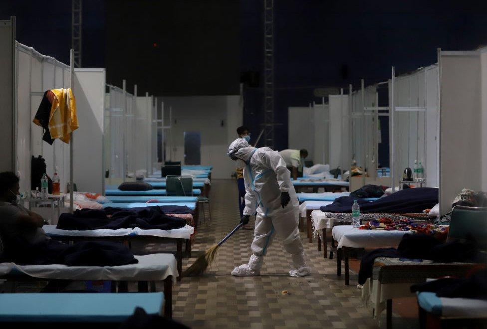 A ward boy sweeping the floor of a ward