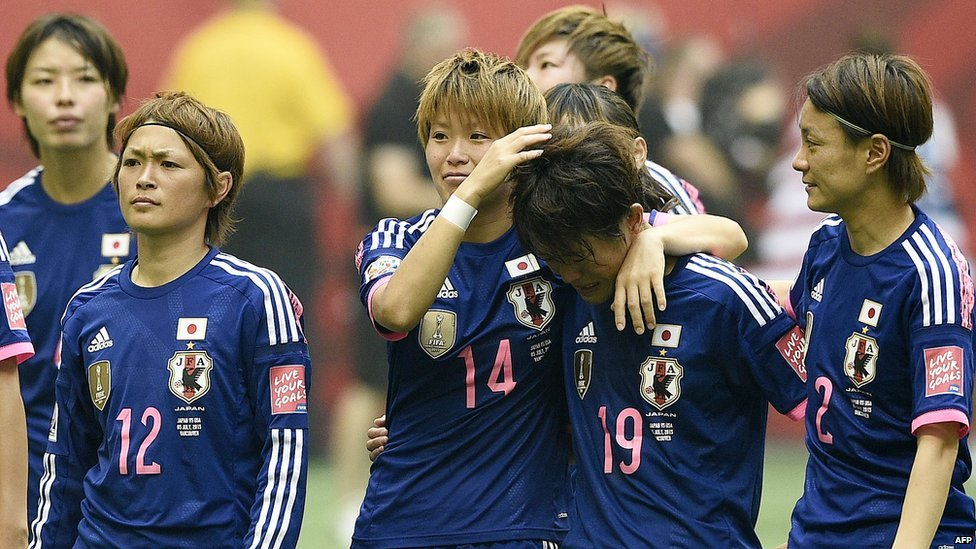Japan's players stand on the pitch after losing the final football match between USA and Japan on 5 July, 2015