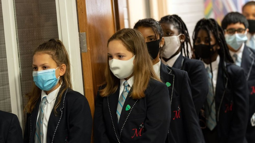 Year eight pupils wear face masks as a precaution against the transmission of the novel coronavirus as they queue in a corridor before attending an English lesson at Moor End Academy in Huddersfield
