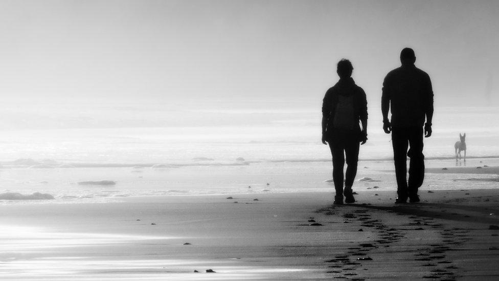 Un pareja en silueta caminando por la playa