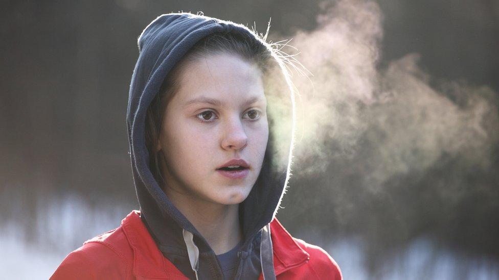 Una joven respira y se observa su aliento por el frío.