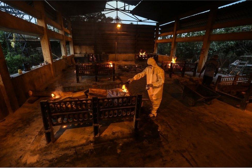 Familiares y empleados municipales practican los ritos fúnebres a las víctimas de covid-19 en un centro de cremación en Bombay, India, 13 de abril de 2021.