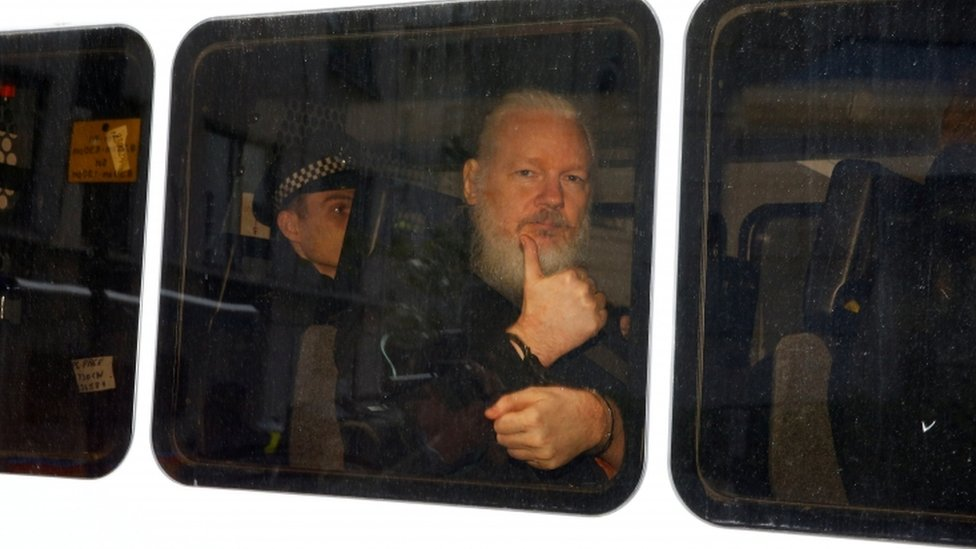 Assange gestures with a thumbs up after he was arrested by Met Police officers at the Ecuador Embassy in London