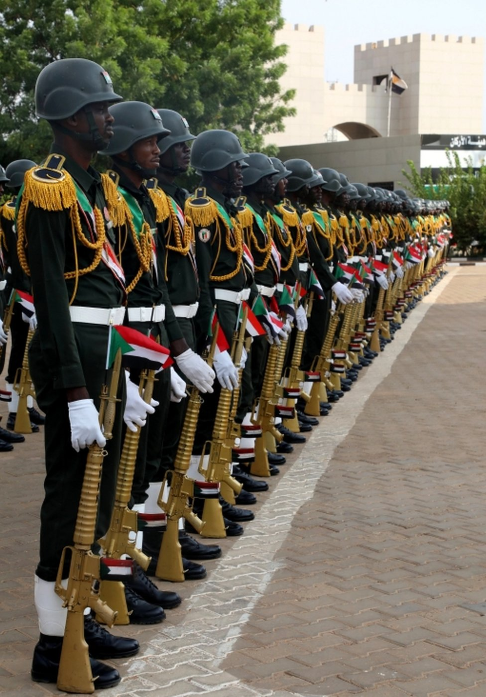 Uniformed military guards holding gold-coloured rifles stand at ease.