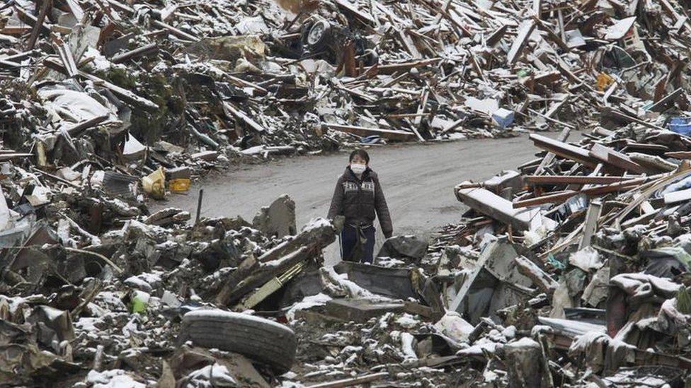 Un mujer camina entre los escombros en el pueblo japonés Minamisanriku, en el norte de Japón, tras el tsunami de 2011.