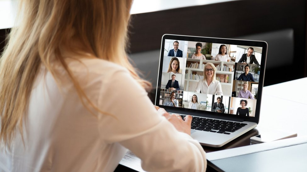 Woman taking part in video conference with laptop showing several faces