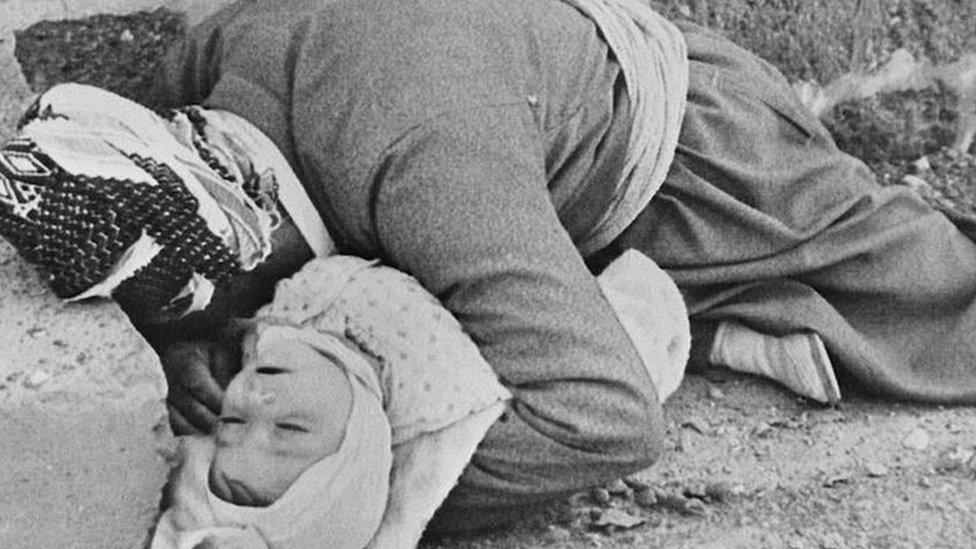 Un padre kurdo sosteniendo a su bebé en sus brazos.
