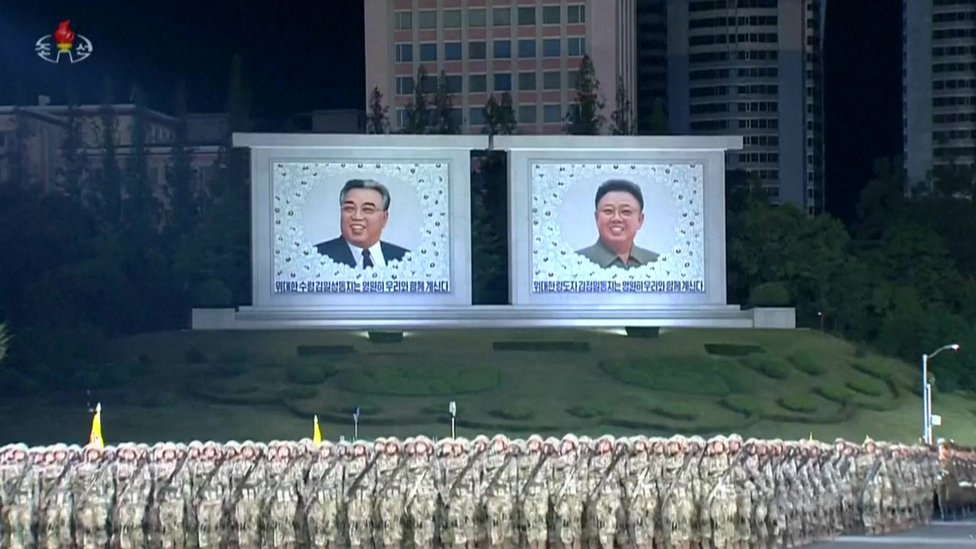 Soldiers stand in front of images of Kim Il-Sung and Kim Jong-il