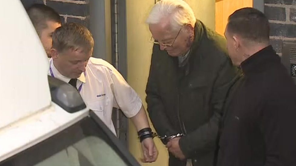 Gordon Anglesea being led away in handcuffs
