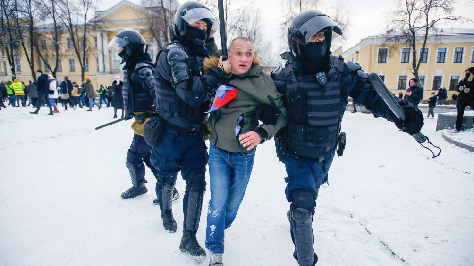 Police officers detain a protester in St Petersburg