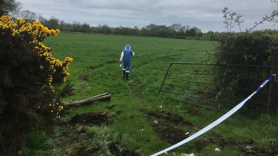 Forensic officer inspects a field near where thieves attempted to steal a cash machine