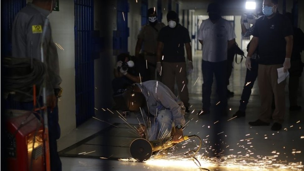 Workers of the Izalco Penitentiary Complex work on the installation of a metal plate in each cell of the prison in Izalco, El Salvador, 27 April 2020.