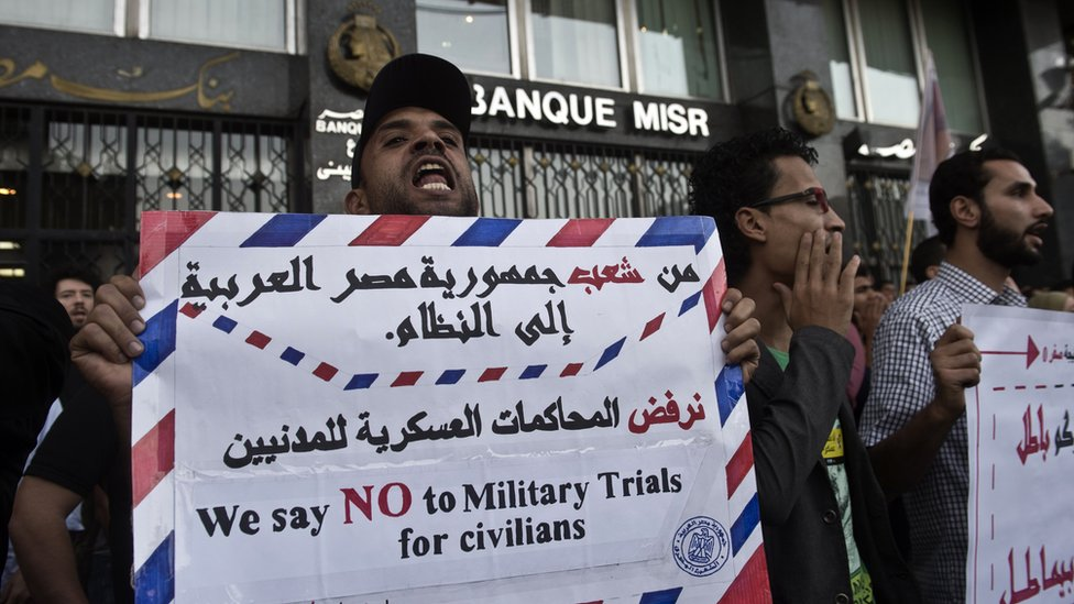 Egyptian protesters hold placards during a protest in Cairo on 26 November 2013