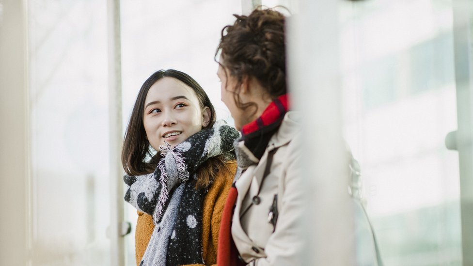 Mujeres hablando en una parada de autobús