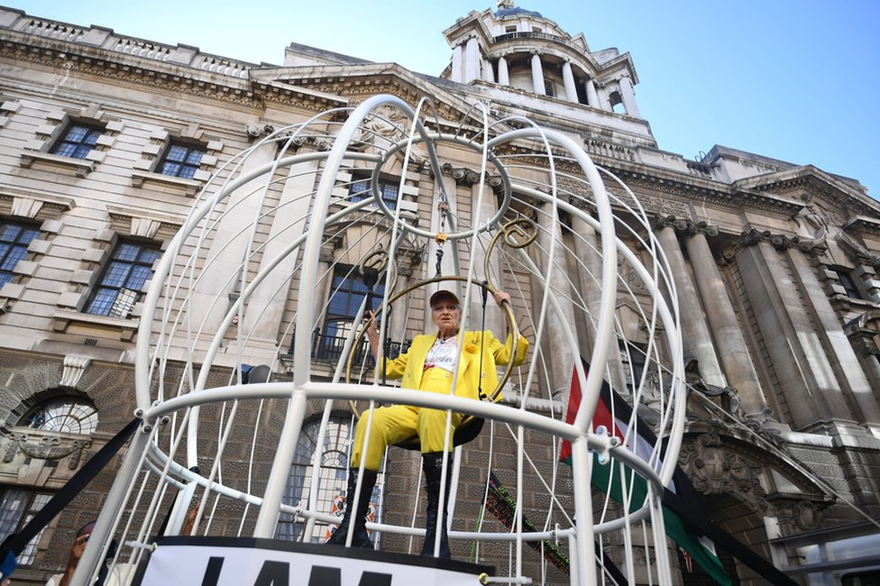 Dame Vivienne Westwood suspended in a large bird cage outside the Old Bailey in London