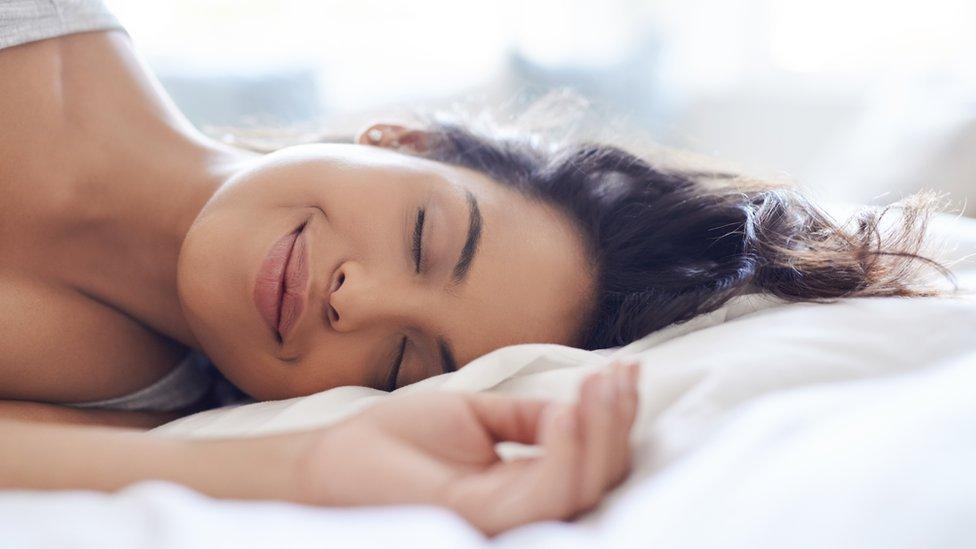 Una mujer duerme en su cama