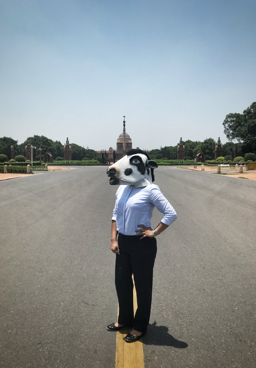 A woman with a cow mask in front of the presidential palace