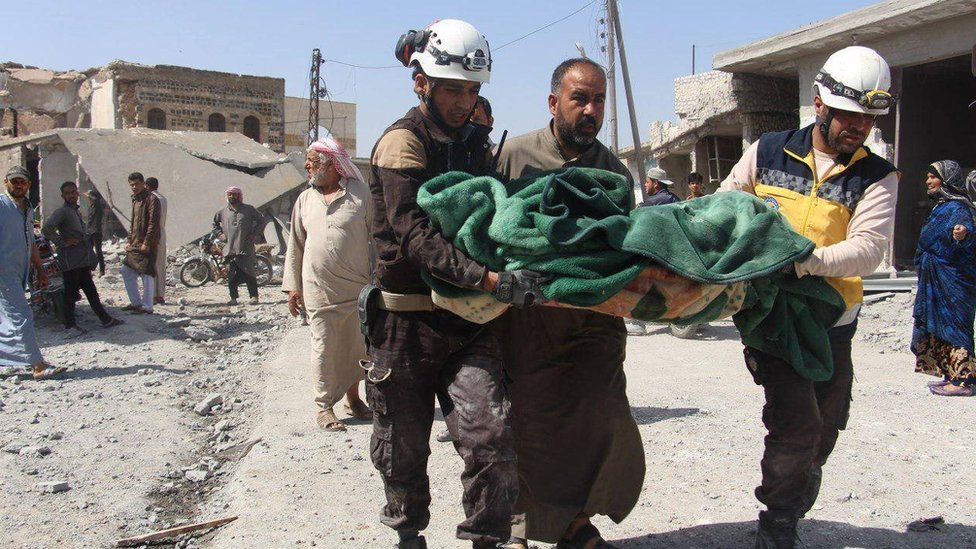 Syria Civil Defence rescue workers help carry the body of a victim of a reported air strike on Ras al-Ain, Idlib province, on 7 May 2019