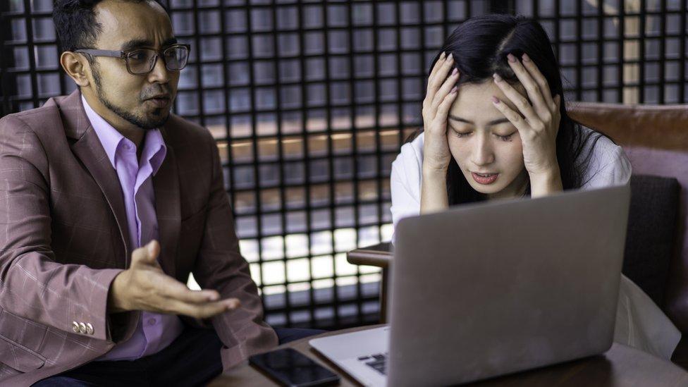 Mujer estresada hablando con un compañero frente a una computadora.