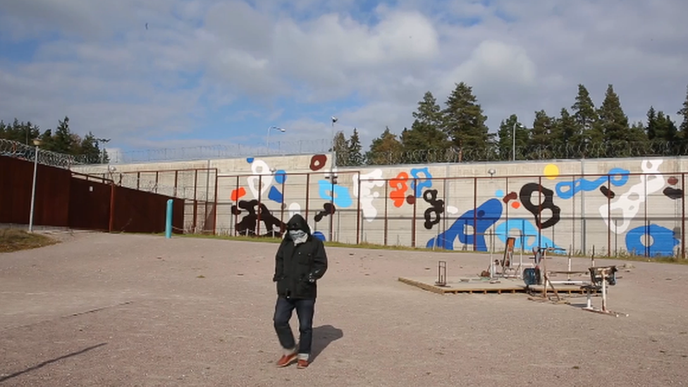 Artist EGS in a Finnish prison yard in front of a mural by him.