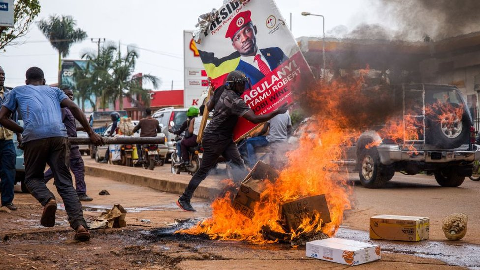 A supporter of Ugandan musician turned politician Robert Kyagulanyi, also known as Bobi Wine, carries his poster as they protest on a street against the arrest of Kyagulanyi